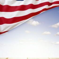 American flag in blue sky above boardwalk